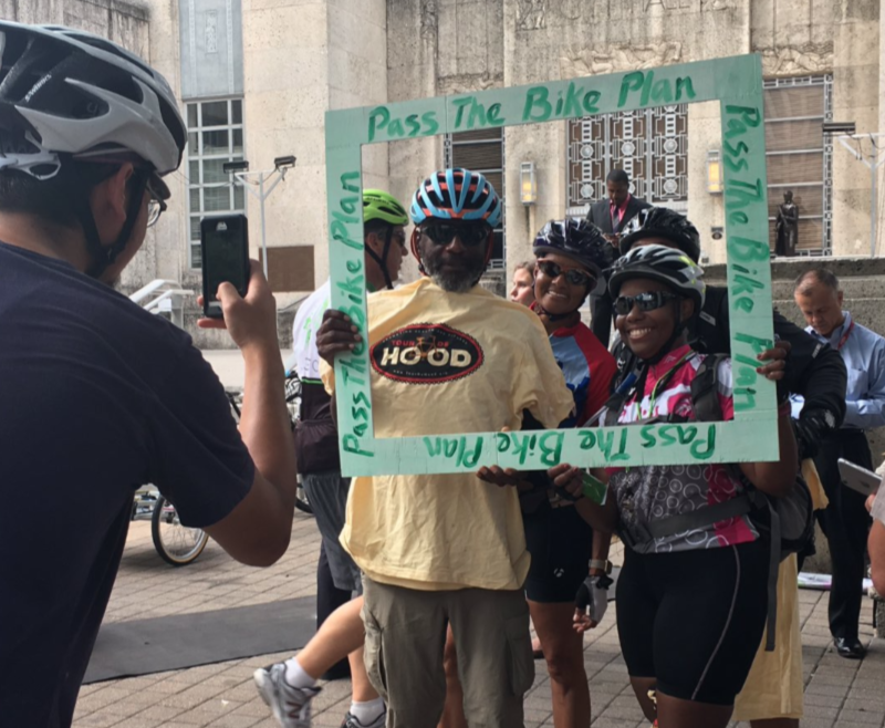 """Supporters set up a selfie frame that says """"Pass the Bike Plan"""""""